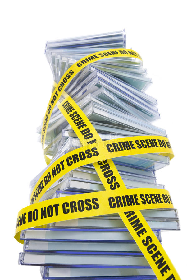 Data piracy. A pile of pirated compact disks wrapped in police tape royalty free stock photos