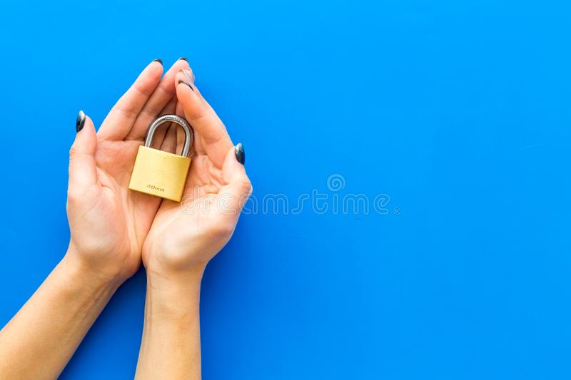 Data protection concept with locker and hands on blue background top view copyspace. Data protection from cyber attack concept with locker and hands on blue stock photography