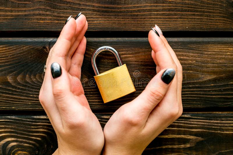 Data protection concept with locker in hands on wooden background top view. Data protection concept with locker in hands on wooden oficce desk background top stock photo