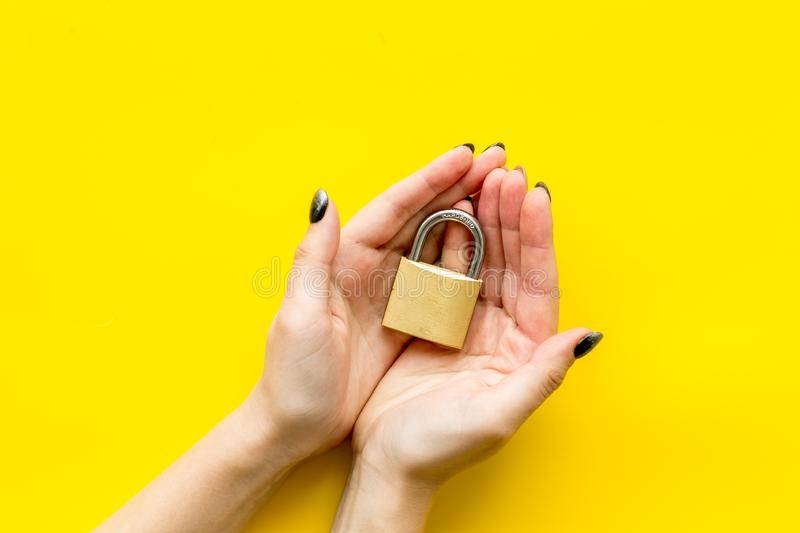 Data protection concept with locker and hands on yellow background top view. Data protection from cyber attack concept with locker and hands on yellow background stock images