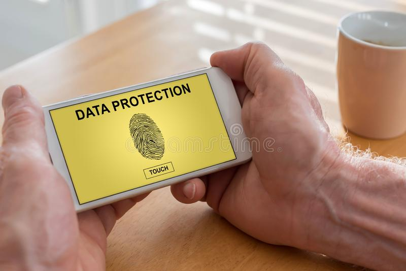 Data protection concept on a smartphone. Male hands holding a smartphone with data protection concept royalty free stock photo