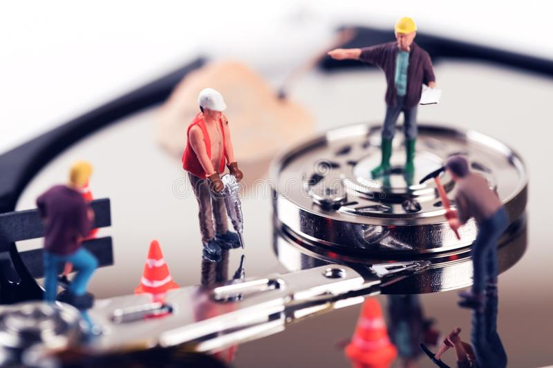 Data recovery concept. construction worker figurines on hard dis royalty free stock image