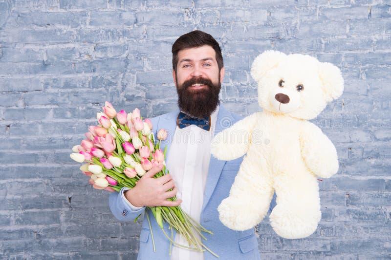 Data rom?ntica preparando-se macho Amor de espera Ramalhete bem preparado das tulipas das flores da posse do laço do smoking do d foto de stock