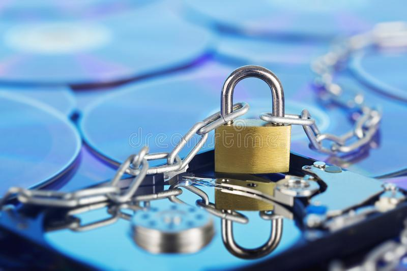 Data security, information protection and personal information defense. Padlock on hard drive disk at CD disk background. Concept. Of digital data and stock photo