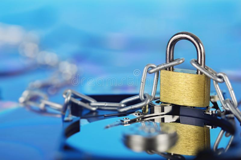 Data security, information protection and personal information defense. Padlock on hard drive disk at CD disk background. Concept. Of digital data and stock images