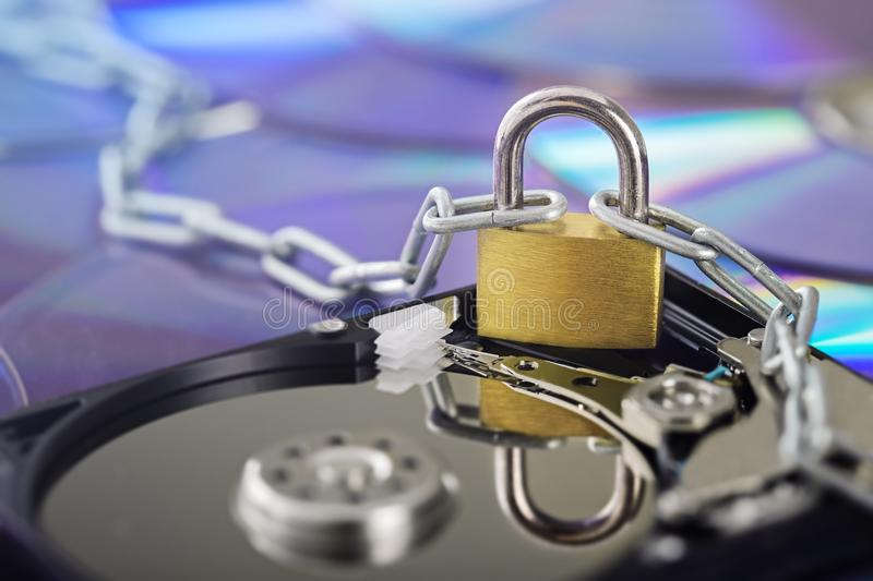 Data security, information protection and personal information defense. Padlock on hard drive disk at CD disk background. Concept. Of digital data and stock image