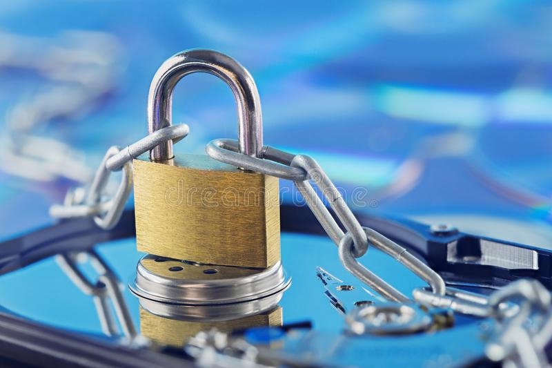 Data security, information protection and personal information defense. Padlock on hard drive disk at CD disk background. Concept. Of digital data and royalty free stock image