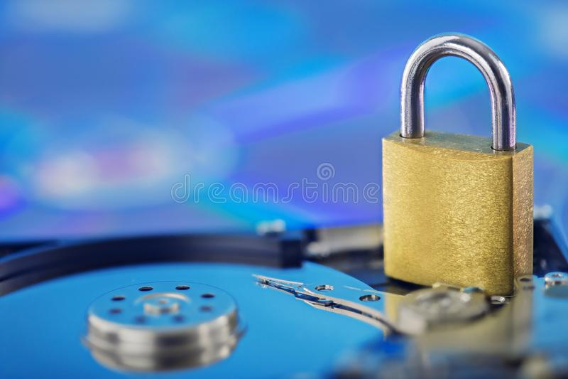 Data security, information protection and personal information defense. Padlock on hard drive disk at CD disk background. Concept. Of digital data and stock photos