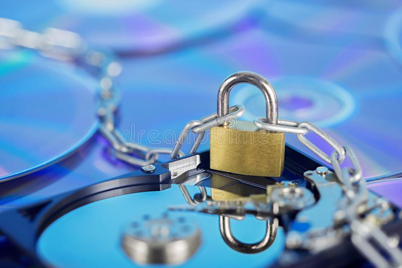 Data security, information protection and personal information defense. Padlock on hard drive disk at CD disk background. Concept. Of digital data and stock photography