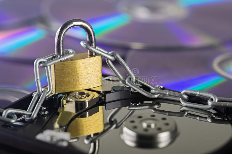 Data security, information protection and personal information defense. Padlock on hard drive disk at CD disk background. Concept. Of digital data and royalty free stock photography