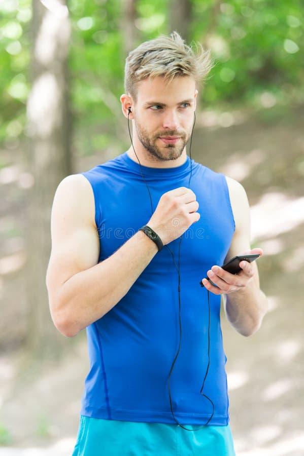 Data synchronization. digital sport. smart watch. athletic man in sportswear. outdoor workout. Fitness app. Ui ux. Concept. gadget in modern sport. muscular man stock photo