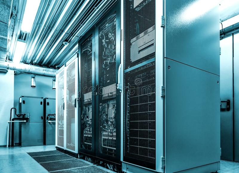 Datacenter有系统计算机的服务器机架在霓虹蓝色定调子 有数的室计算机主机硬件和巨型计算机  库存照片