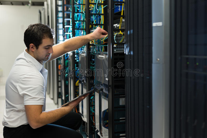 Datacenter manager. A confident datacenter manager working on a computer tablet with a smile