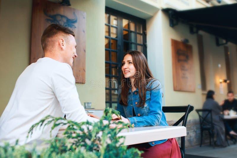Datación del hombre y de la mujer en café Café de consumición de los pares felices en café del aire libre el vacaciones de verano fotos de archivo