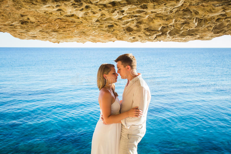 Datación romántica Pares cariñosos jovenes que caminan junto por la playa que goza del mar foto de archivo