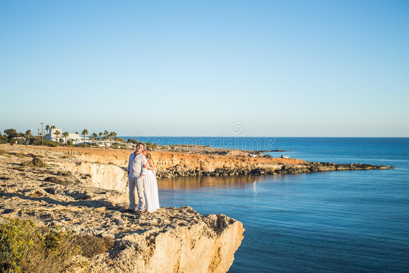 Datación romántica Pares cariñosos jovenes que caminan junto y que gozan del mar imagen de archivo