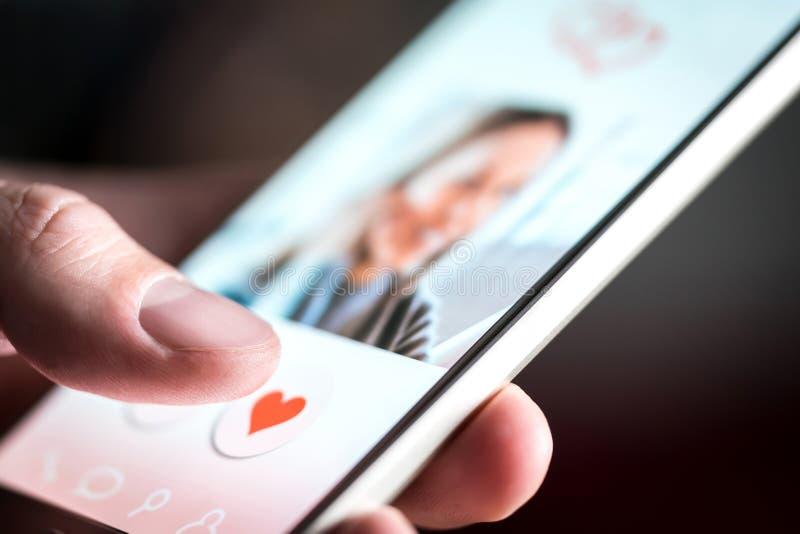 Datando o app ou o local na tela do telefone celular Homem que swiping e que gosta de perfis foto de stock