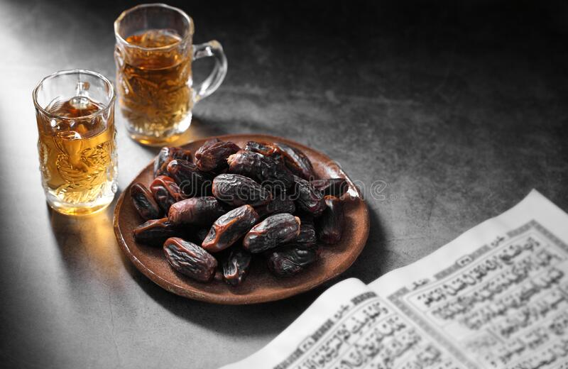 Datas de frutas e livro islâmico do Corão em contexto concreto imagem de stock royalty free