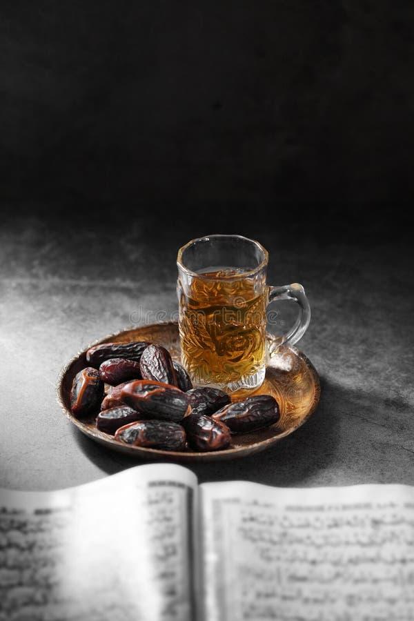 Datas de frutas e livro islâmico do Corão em contexto concreto foto de stock royalty free