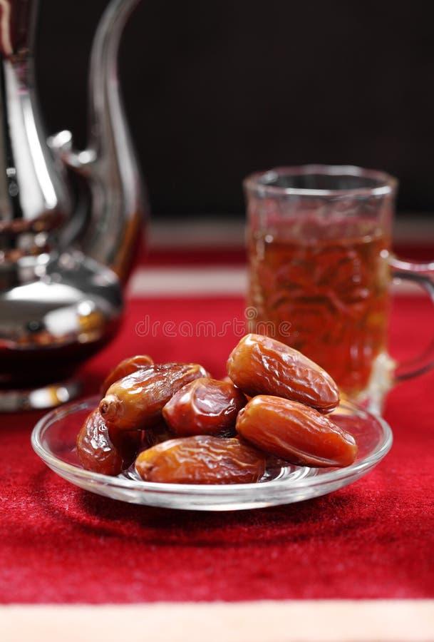 Datas do fruto e do Livro Islâmico do Corão em fundo de tapete imagens de stock