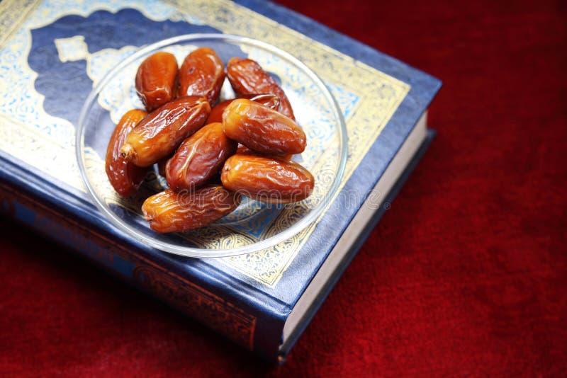 Datas do fruto e do Livro Islâmico do Corão em fundo de tapete fotos de stock