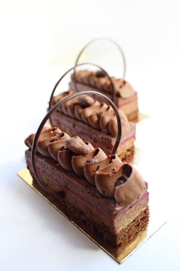 Datas e fatias da sobremesa do bolo de chocolate em pousas-copos douradas fotografia de stock