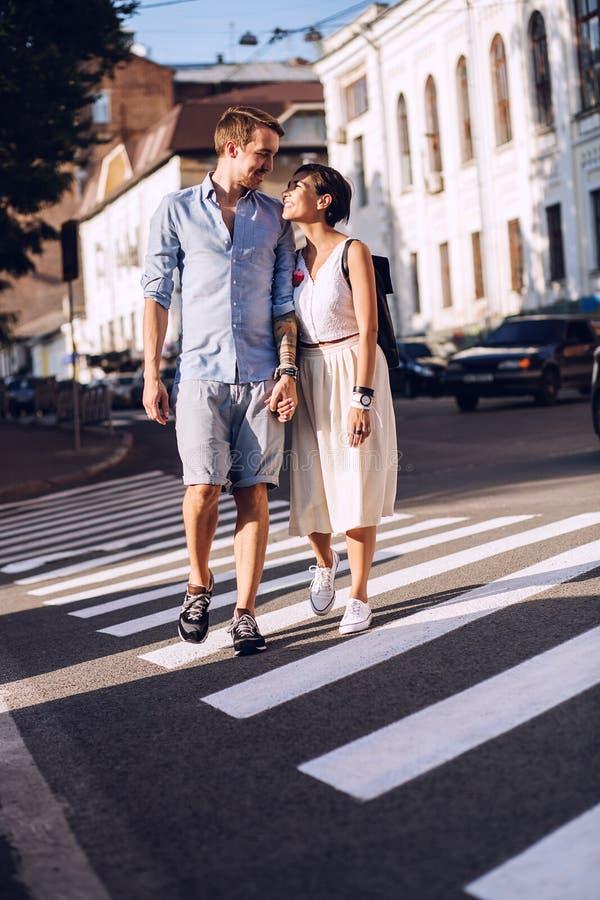 Datation de sourire de couples dans la ville, marchant sur le passage piéton images stock