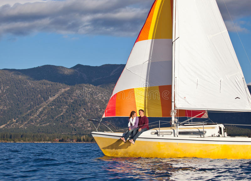 A Date on a Boat. A couple having a date on the front deck of a sailboat, enjoying a light Lake Tahoe breeze. Photo taken from a kayak