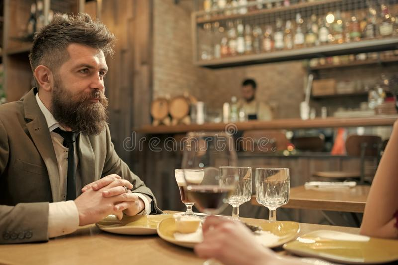 Date or business meeting of hipster in pub. Confident bar customer speak in cafe. Businessman with long beard in cigar royalty free stock photos