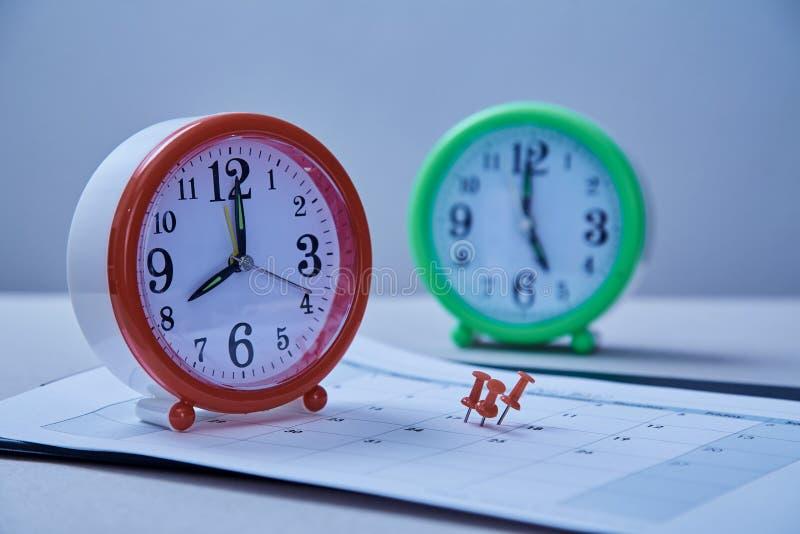 Date-butoir de gestion du temps et concept de programme : autocollants collés sur l'horloge de table et la punaise rouge photographie stock