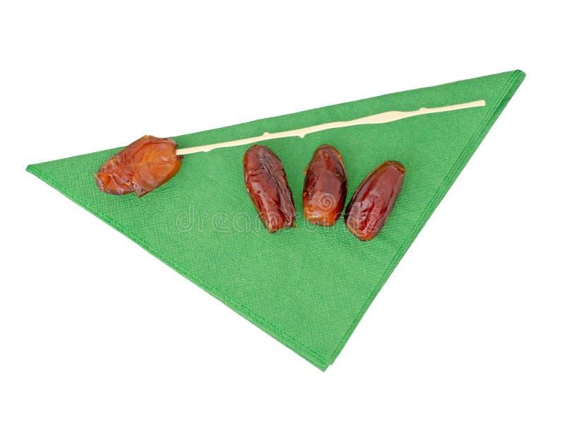 Date con il bastone di plastica, gambo, sul tovagliolo del Libro Verde, tovagliolo, isolato su fondo bianco Natale tradizionale B immagini stock