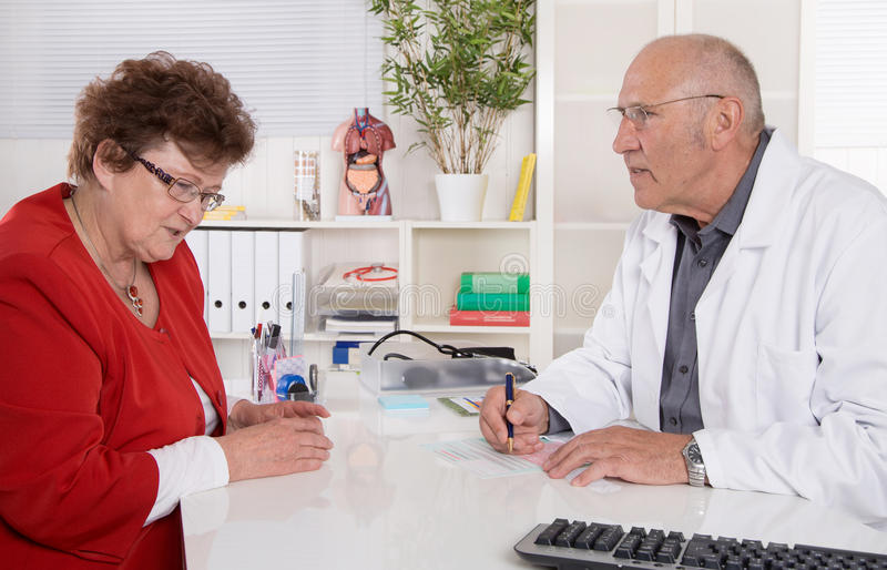 Date at doctor: older woman ill and has pains. Portrait: older doctor with experience talking with senior women sitting at desk royalty free stock photo