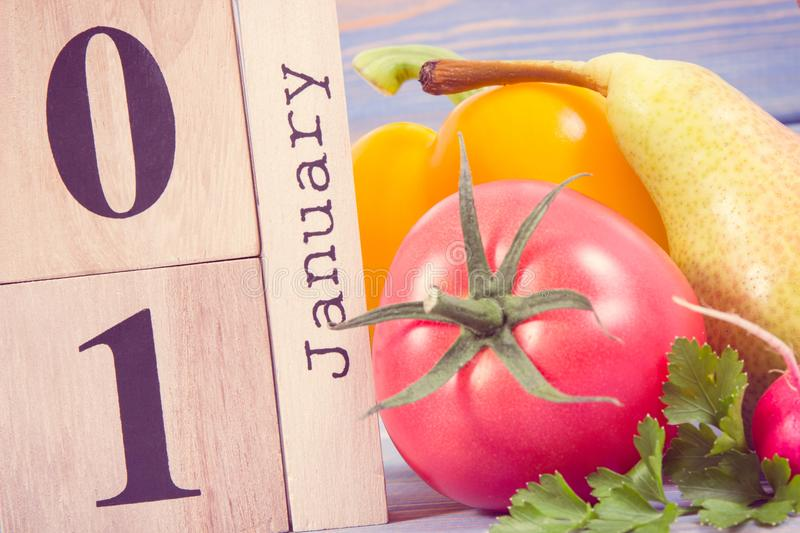 Date 1 January on calendar and fresh fruits with vegetables, new years resolutions of healthy nutrition concept. Date 1 January on cube calendar and fresh ripe stock image