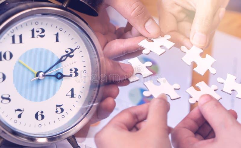 Date limite de comptage de l'horloge avec l'équipe mettant en place le jigsaw pour le concept de travail de l'équipe d'échéance d photos stock