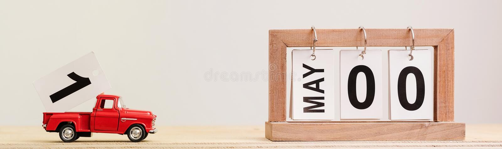 Date is May 1. A red toy truck carries the number one to the flip calendar. Date is May 1 royalty free stock images
