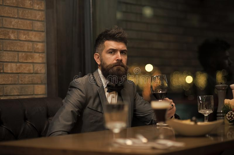 Date meeting of hipster awaiting in pub. Perfect wine. Businessman with long beard drink in cigar club. Bearded man rest stock photo