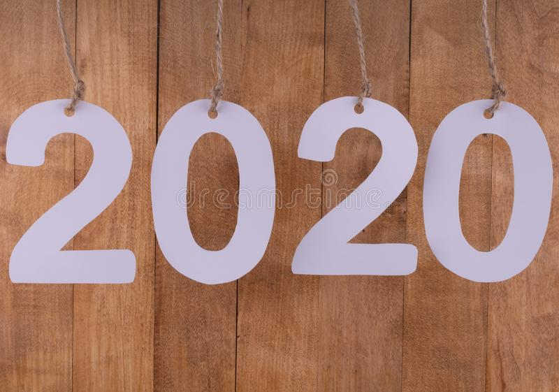 the date of the new two thousand and twentieth year is highlighted in close-up by numbers hanging on ropes on a brown background royalty free stock photos