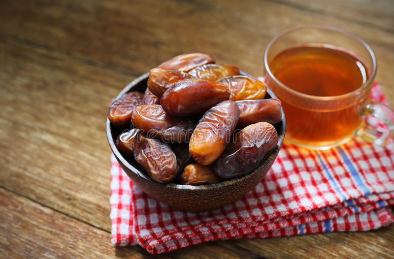 Date-palm in wood bowl with cup of tea on wood stock photos