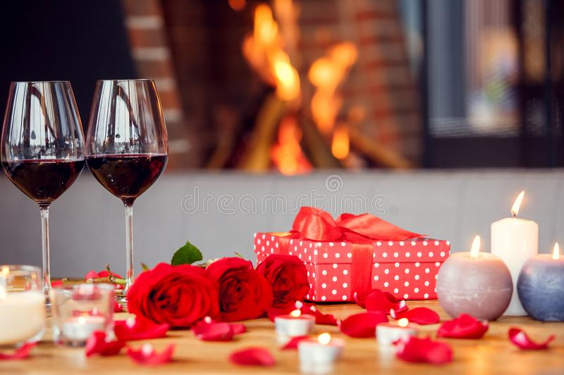 Date in restaurant decorated table with roses and present box no people close-up. Romantic date objects in restaurant decorated table with three red roses and stock photography