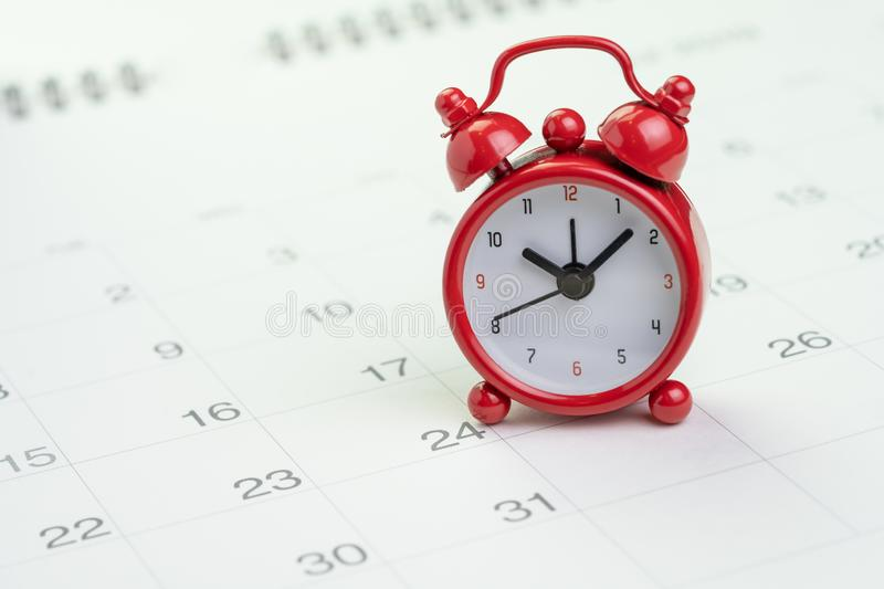 Date and time reminder or deadline concept, small red alarm clock on white clean calendar with number of day, counting down to stock photos
