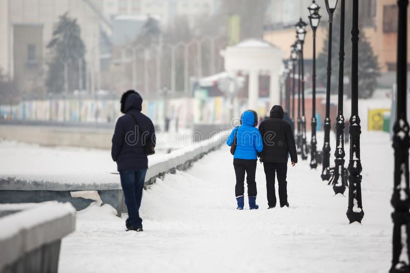 A date in the winter on the waterfront. People walk in the snow on the street. A couple in love royalty free stock images