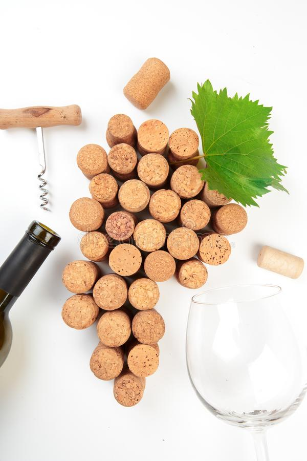 Dated and vintage wine corks in the shape of a group of grapes with a green leaf on white background. - Image stock photography