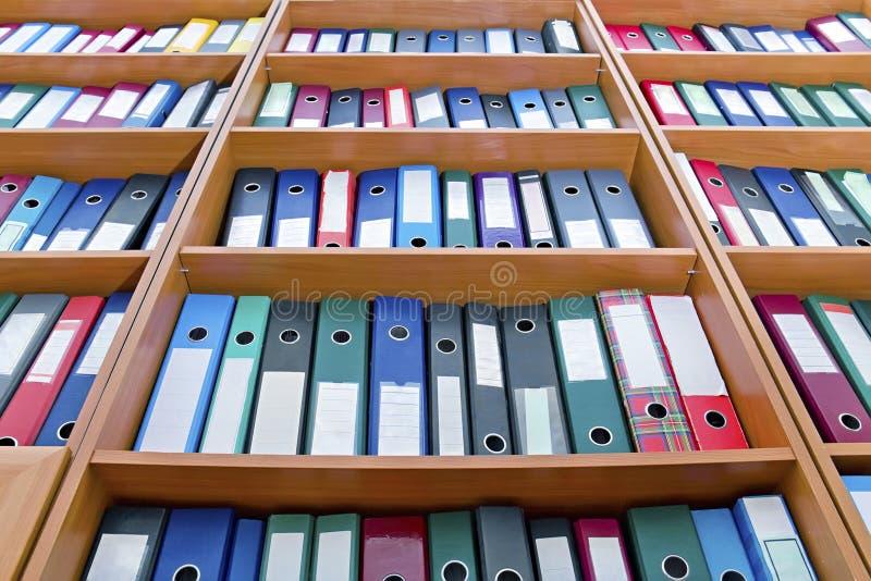 Dateifaltblätter, stehend auf den Regalen stockbilder