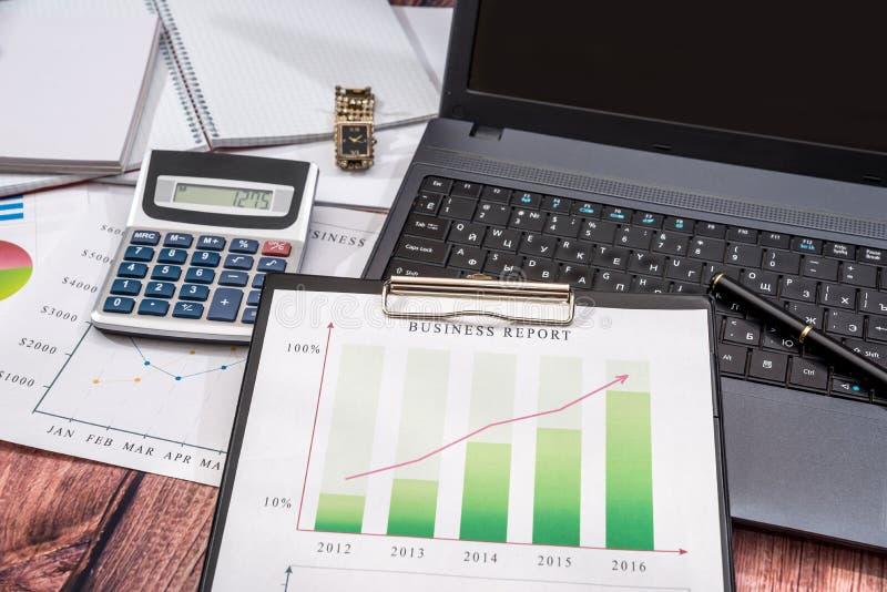 Daten bezüglich der Diagramme und der Diagramme mit Laptop und Notizblock auf Schreibtisch, lizenzfreie stockfotos