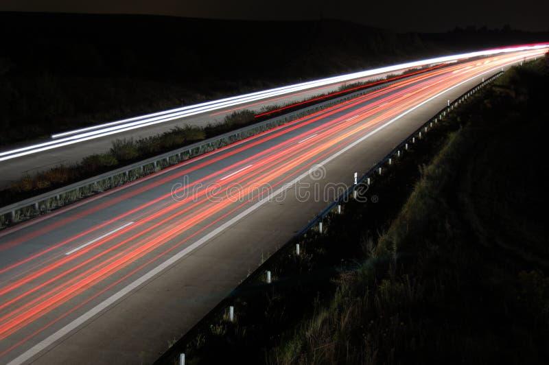 Datenbahn nachts mit Verkehr lizenzfreie stockfotos