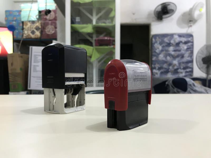Dater d'imprimante encré deux par individus sur un bureau beige dans le lieu de travail photographie stock