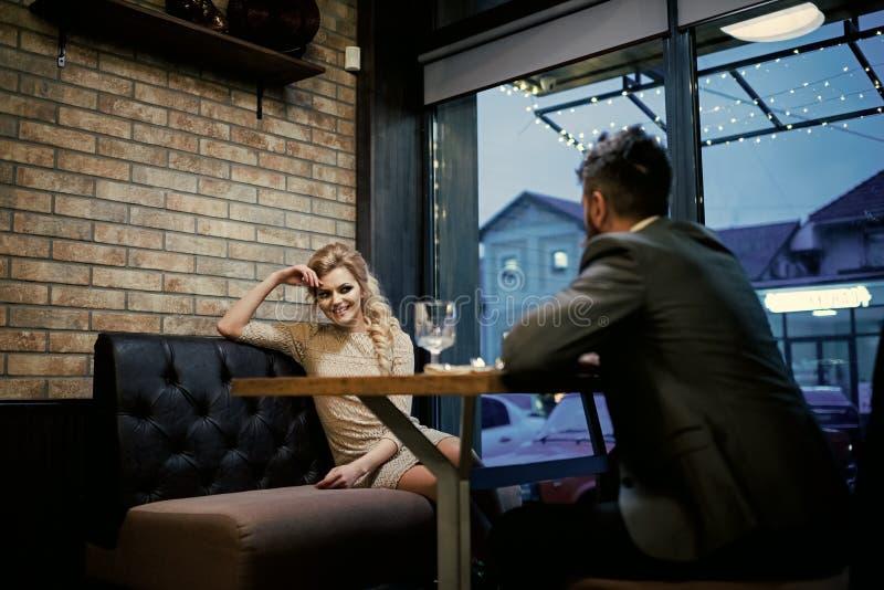 Datera ett älska par Par som är förälskade på restaurangen Valentindag med den sexiga kvinnan och den skäggiga mannen Förslag och arkivbilder