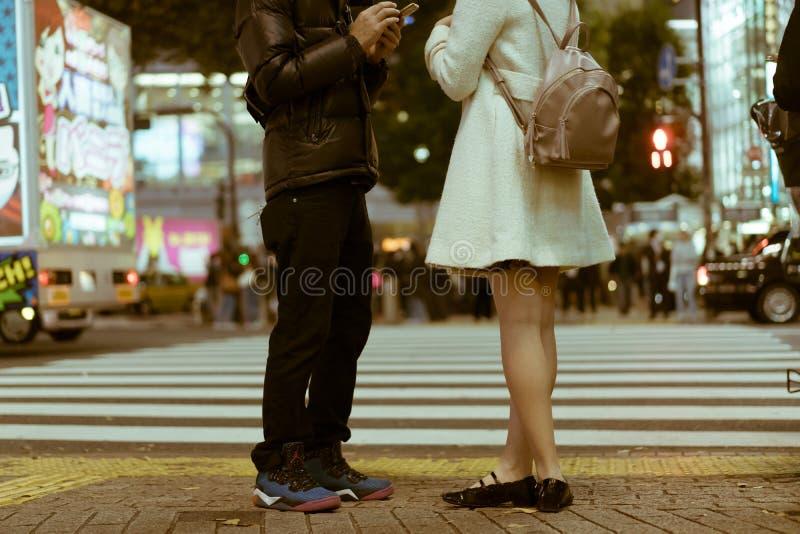 Daterend paar die zich door Shibuya bevinden die en telefoonaantallen in Tokyo, Japan kruisen ruilen stock foto