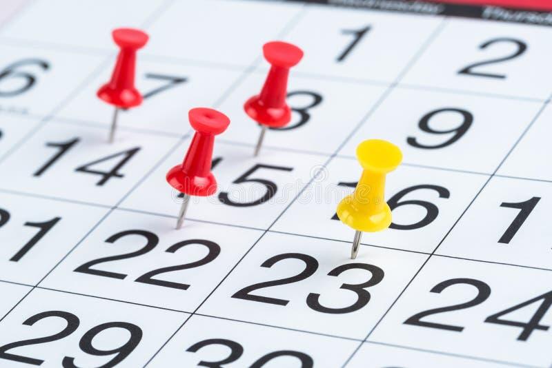 Dates accentuées par des punaises sur un calendrier image stock