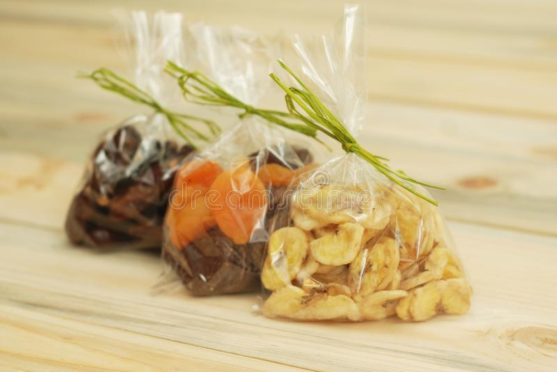Dates, dried apricots, prunes, raisins on wooden background. Dried Fruits for Gift. royalty free stock photo